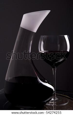 Red wine in decanter with a full glass with wine beside isolated on dark background