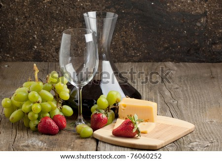 Red wine in decanter with grapes, strawberries and cheese on old wooden table