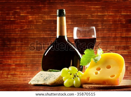 Red wine in fine glass with cheese and grape