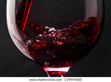 Red wine in wineglass on a black background