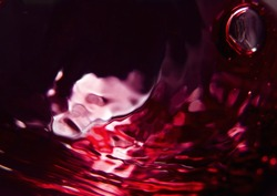 Red wine on a black background, abstract splashing.