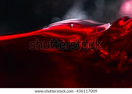 Red wine on black background, abstract splashing.