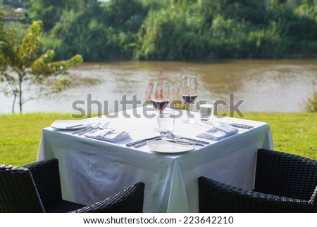 red wine on table set and  green grass background in the garden