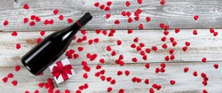 Red wine plus giftbox with little red lovely hearts on white rustic natural wood in flay lay composition for Valentines Day concept