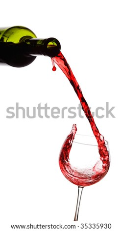 Red wine pouring down from a wine bottle against white background - stock photo