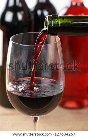 Red wine pouring from a bottle into a wine glass.