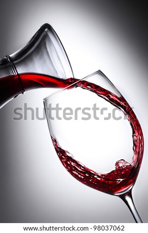red wine pouring from carafe into glass