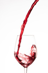 Red wine pouring in a wine glass, on a white background