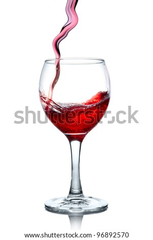 Red wine pouring in glass isolated on white background