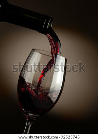 Red wine pouring in glass over dark background