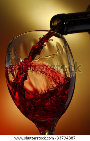 Red wine pouring into a glass, with abstract background