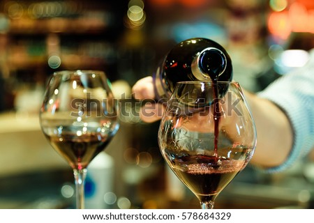 Red wine pouring into a wine glass. Shallow depth of field. #578684329
