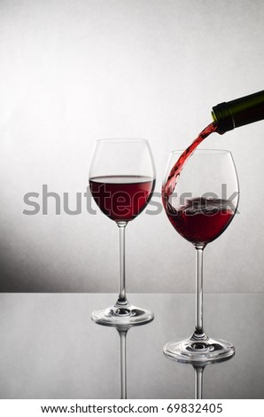 Red wine pouring into glass close up - stock photo