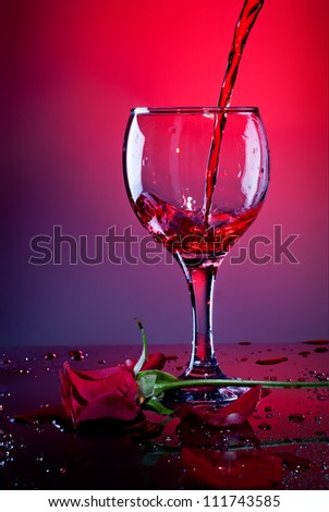 Red wine pouring into wine glass and red rose