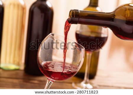 Red wine pouring into wine glass, close-up. Flat mock up for design.