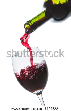red wine pouring into wine glass isolated