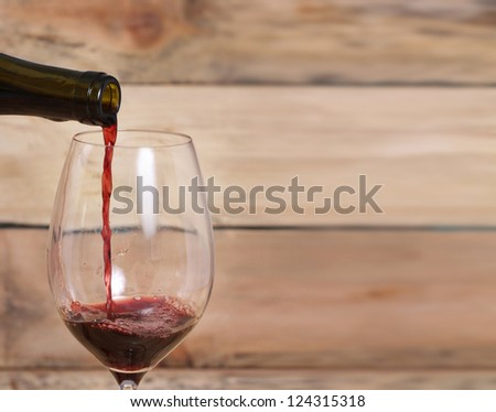 Red Wine Pouring on a wood background