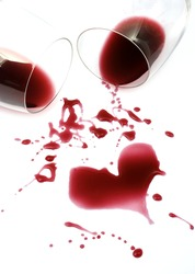 Red wine spilled from glasses forming a heart shape on white background
