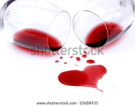 Red wine spilled from glasses forming heart shape