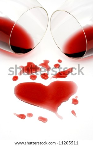 Red wine spilled from two glasses, forming a heart shape