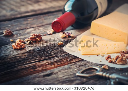 Red Wine, Walnuts and Cheese on Wooden Table. Rural Style