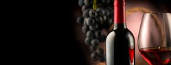 Red wine. Wine. Bottle and glass of Red wine with ripe grapes still life. Red wine Over black background. Wide angle Border art design with space for your text