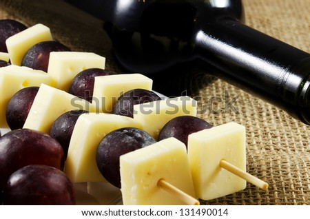 Red wine with cheese and red grapes close up image