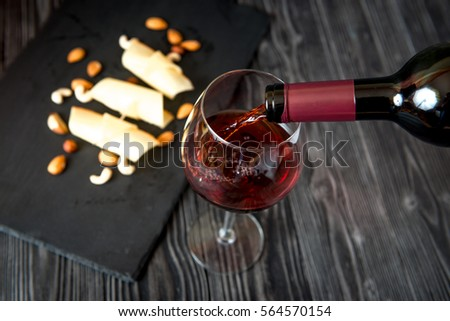 red wine with cheese on wooden background top view