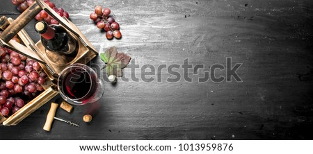 Red wine with fresh grapes in a box. On the black chalkboard.