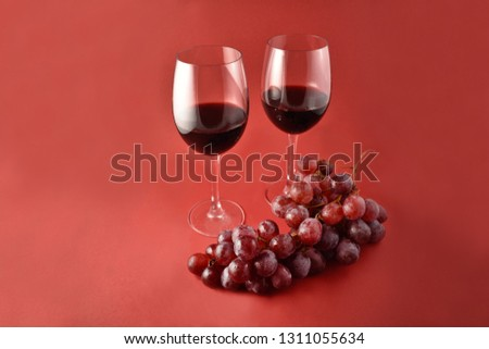 Red wine with grapes stock images. Two glasses of red wine. Red wine on a red background #1311055634