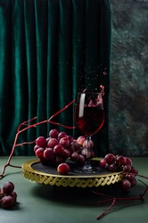 Red wine with red grapes on a gold tray. Splashing wine. Photo in modern style.