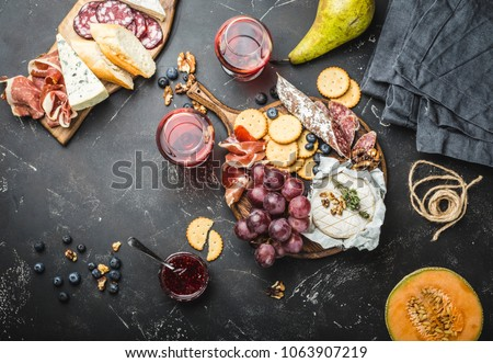 Red wine, wooden boards, cold meat, variety of cheese, fruit, bread, dip. Stone background. Delicatessen plate. Mix of different snacks/appetizers. Top view. Fruit, cheese, meat, wine. Party food