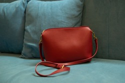 Red women's leather bag with gold fittings on a turquoise blue sofa. A minimalistic contrast wardrobe concept with a bold accent. Fashionable trending accessory for a stylish girl. Copy space
