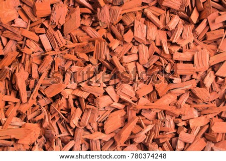 Red wood chips. Natural texture background of red wooden pieces of tree bark. Wood chips, mulch for gardening or natural themes. Full filled frame picture. Landscaping red colored materials.Above view