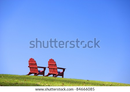 Red wooden Adirondack style chairs are sitting on a green grassy hillside. Horizontal shot.