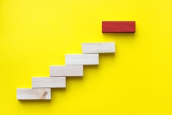 Red wooden block on yellow. Business planning, Risk Management, Solution, leader, strategy, different and Unique Concepts. Wood block stacking as step stair. Concept for business growth success proces
