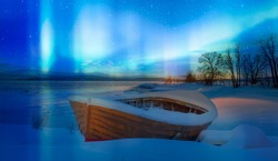 Red wooden boat covered with layers of snow - Aurora Borealis in Tromso, Norway in front of the Norwegian fjord