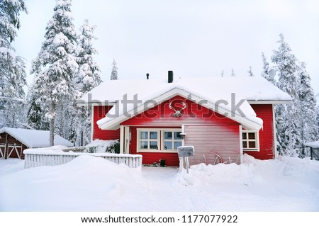 red wooden cottage in a snow landscape