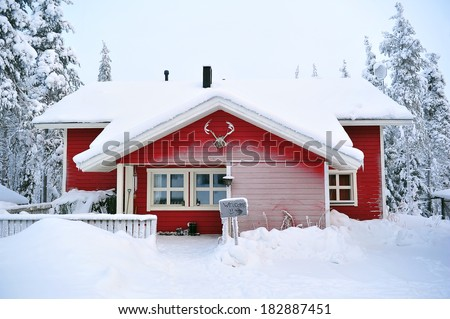 red wooden cottage in a winter landscape