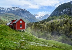 Red wooden cottage in the valley. Green grass, white flowers. Stone snowy mountains. Stalheim, Norway. Lightly mist.