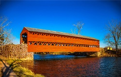 Red wooden covered bridge over the river. Covered bridge over river. River covered bridge. Red covered bridge over river