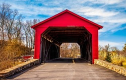 Red wooden covered bridge over the river. Covered bridge road. Red covered bridge view. Covered bridge entrance