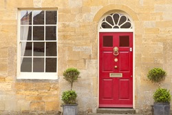 Red wooden doors in an old traditional English stone cottage with two plant pots in front .