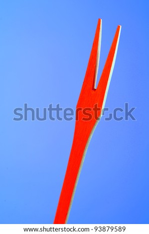 Red Wooden Fork on Blue Background with Copy Space