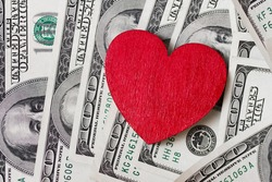 red wooden heart and many greenbacks one hundred dollar dollars with image of Franklin scattered on the surface