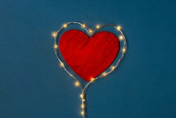 Red wooden Heart laid out of strand lights on a blue background.. The concept of hot love. Valentine's Day blank for congratulations