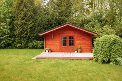 Red wooden house in a garden with a lot of green trees and lawn. Vacation in the country. Big wooden hut in the forest