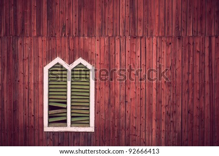 Red wooden rustic wall with window and broken shutters