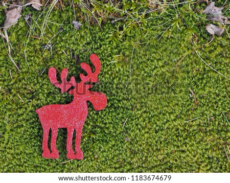 Red wooden silhouette of moose, or elk, or deer, lies on lush green forest, swamp moss with dry grass on top edge of picture; with copy space