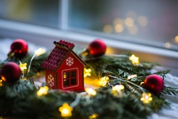 Red wooden toy house surrounded with fir-tree wreath decorated with warm garland lights and little Christmas balls near window. New Year festive glowing decoration. Concept of cozy home in winter.
